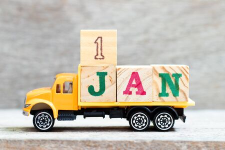 Truck hold letter block in word 1jan on wood background (Concept for date 1 month January) First day of the new year Reklamní fotografie