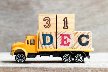 Truck hold letter block in word 31dec on wood background (Concept for date 31 month December)
