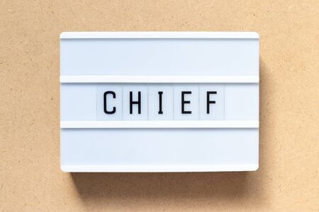 White lightbox with word chief on wood background