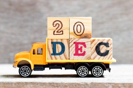 Truck hold letter block in word 20dec on wood background (Concept for date 20 month December) Stockfoto