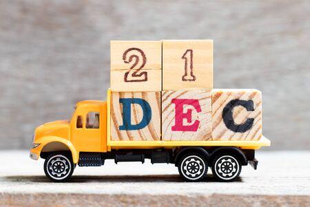 Truck hold letter block in word 21dec on wood background (Concept for date 21 month December) Stockfoto