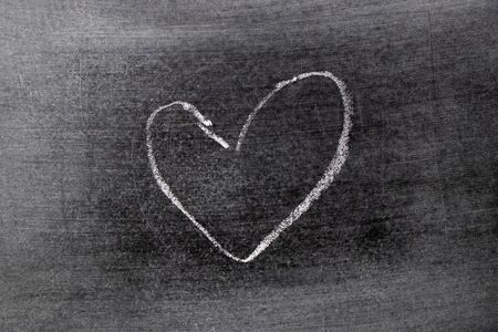White color chalk hand drawing in heart shape on blackboard background Stockfoto
