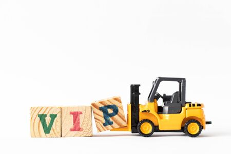 Toy forklift hold wood letter block P to complete word VIP (Abbreviation of very important person) on white background