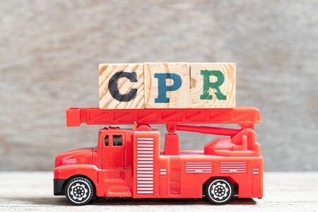 Red fire truck hold letter block in word CPR (abbreviation of Cardiopulmonary resuscitation) on wood background
