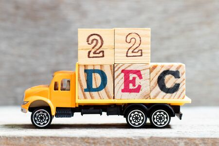 Truck hold letter block in word 22dec on wood background (Concept for date 22 month December)
