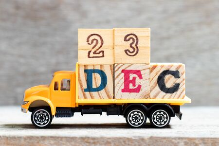 Truck hold letter block in word 23dec on wood background (Concept for date 23 month December)