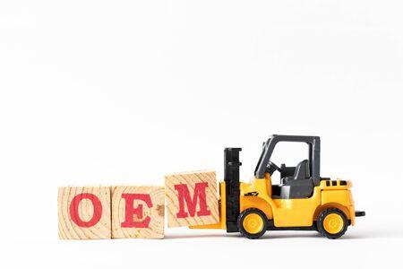 Spielzeuggabelstapler halten Holzbuchstabenblock M, um das Wort OEM (Abkürzung des Originalgeräteherstellers) auf weißem Hintergrund zu vervollständigen