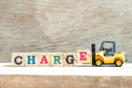 Toy forklift hold letter block e to complete word charge on wood background