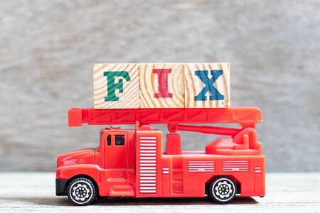 Red fire truck hold letter block in word fix on wood background