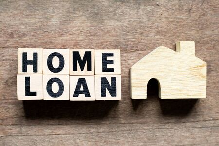 Letter block with word home loan and home model on wood background