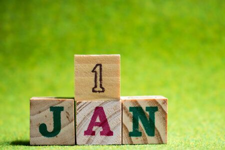 Letter block in word 1jan on artificial green background (Concept for calendar date in 1 month January, the first date of new year)