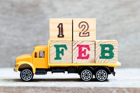 Truck hold letter block in word 12feb on wood background (Concept for date 12 month February)