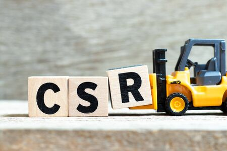 Toy forklift hold letter block r to complete word CSR (Abbreviation of corporate social responsibility) on wood background