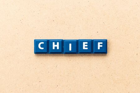 Tile letter in word chief on wood background
