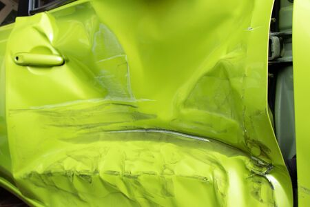Closed up background  of damaged green color door of car that caused from accident
