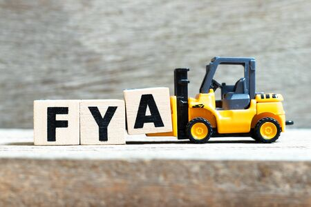 Toy forklift hold letter block A to complete word FYA (Abbreviation of For your action or attention) on wood background Foto de archivo - 135243727