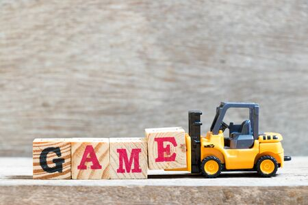 Toy forklift hold letter block e to complete word game on wood background