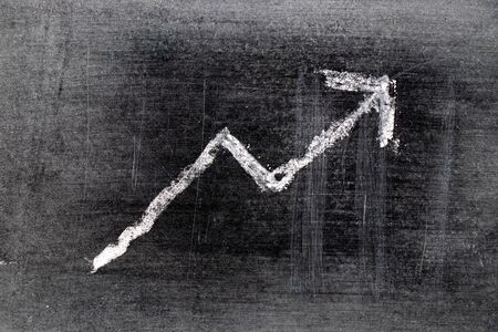 White chalk draw as upward arrow graph on black board background (Concept for sale, profit, cost of company in uptrend)