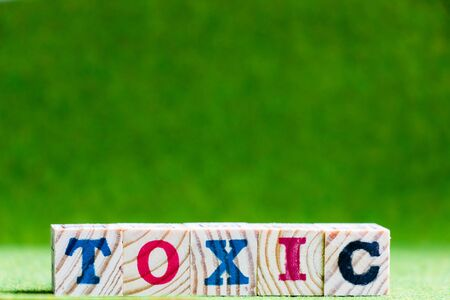 Letter block in word toxic on artificial green background