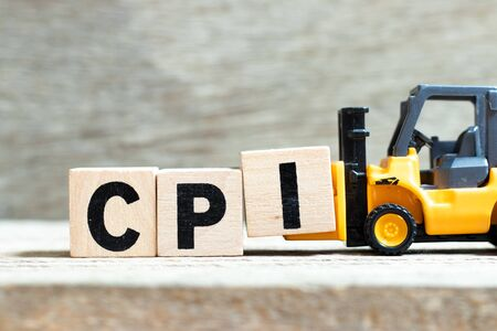 Toy forklift hold letter block I to complete word CPI (abbreviation of Consumer Price Index) on wood background