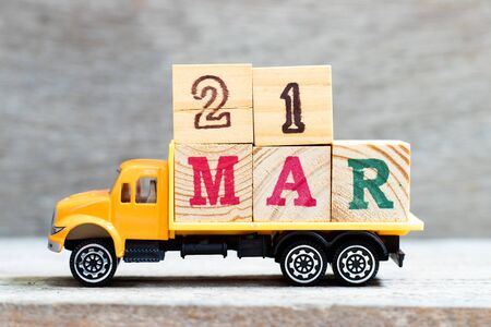 Truck hold letter block in word 21 mar on wood background (Concept for date 21 month March)