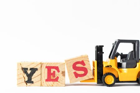 Toy forklift hold wood letter block s to complete word yes on white background