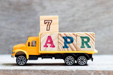 Truck hold letter block in word 7 apr on wood background (Concept for date 7 month April)