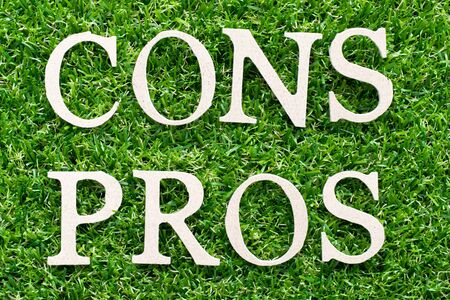 Wood alphabet in word pros cons on artificial green grass background