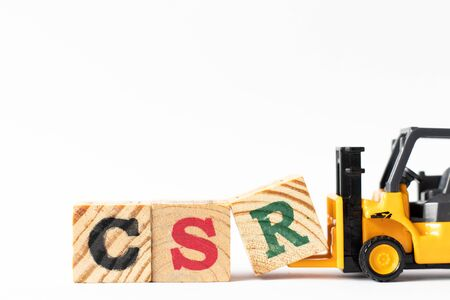 Toy forklift hold wood letter block R to complete word CSR (Abbreviation of corporate social responsibility) on white background