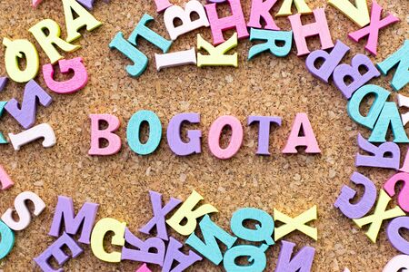 Color alphabet in word Bogota with another letter as frame on cork board background