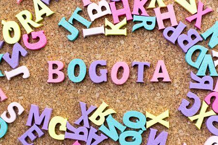Farbalphabet im Wort Bogota mit einem anderen Buchstaben als Rahmen auf Korkbretthintergrund