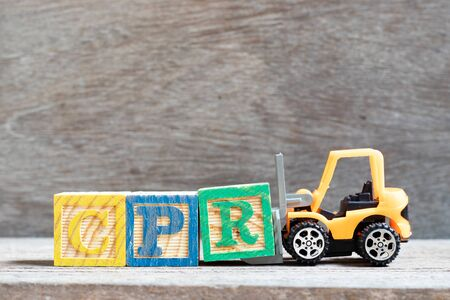 Toy forklift hold letter block r to complete word CPR (abbreviation of Cardiopulmonary resuscitation) on wood background