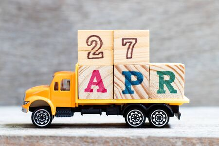 Truck hold letter block in word 27apr on wood background (Concept for date 27 month April)