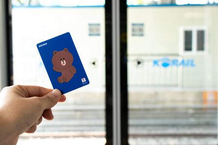 Seoul, South Korea- Oct 21, 2019  : Traveller hand hold t money card with line cartoon character on defocused Korail clear door for train transportation