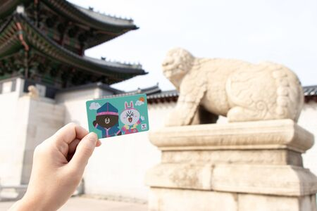 Seoul, South Korea- Sep 25, 2019 : Traveller hand hold t money card with line cartoon character on defocused Haechi statue in front of gyeongbokgung palace