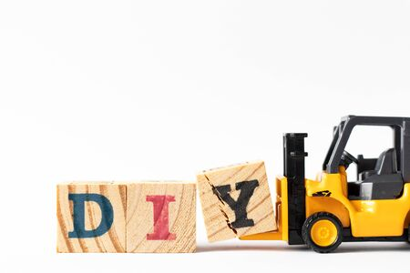 Toy forklift hold wood letter block Y to complete word DIY (Abbreviation of Do it yourself) on white background Фото со стока