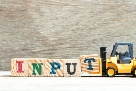 Toy forklift hold letter block t to complete word input on wood background Stock fotó