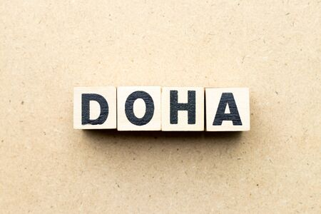 Letter block in word Doha on wood background Фото со стока