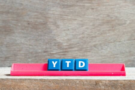 Tile letter on red rack in word YTD (abbreviation of year to date) on wood background