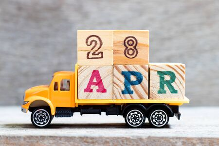 Truck hold letter block in word 28apr on wood background (Concept for date 28 month April)