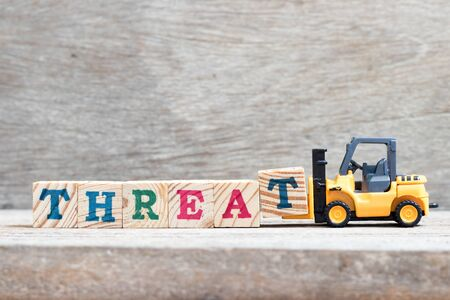 Toy forklift hold letter block t to complete word threat on wood background
