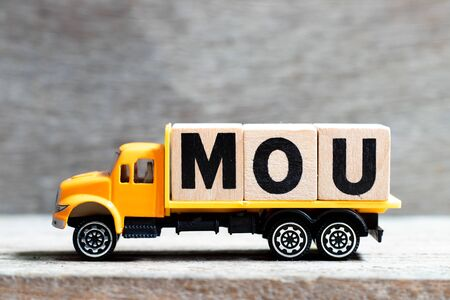 Truck hold letter block in word MOU (Abbreviation of memorandum of understanding) on wood background