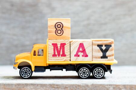 Truck hold letter block in word 8may on wood background (Concept for date 8 month May)