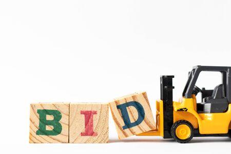 Chariot élévateur jouet tenir le bloc de lettre en bois D pour compléter l'offre de mot sur fond blanc Banque d'images