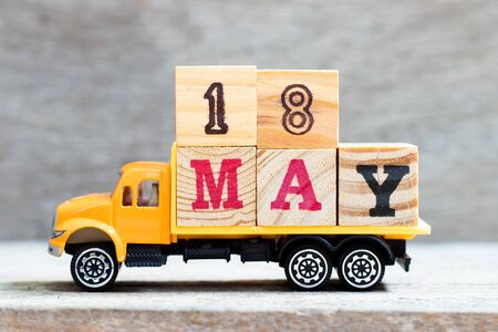 Truck hold letter block in word 18 may on wood background (Concept for date 18 month May)