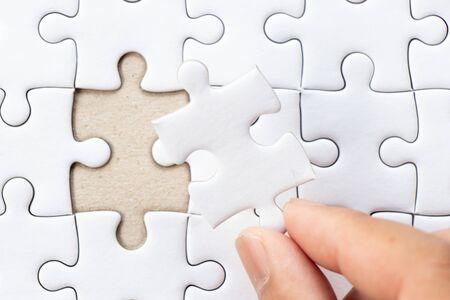 Gesloten achtergrond van witte duidelijke puzzel met hand die ontbrekend stuk houdt om te passen of te vervullen