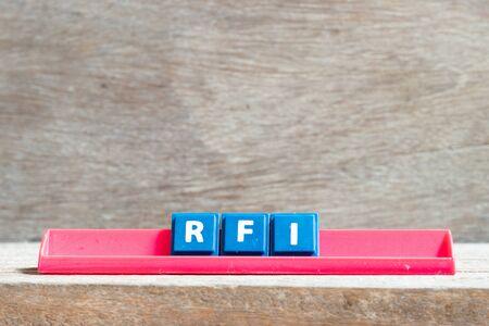 Carta de mosaico en rack rojo en word RFI (abreviatura de solicitud de información) sobre fondo de madera