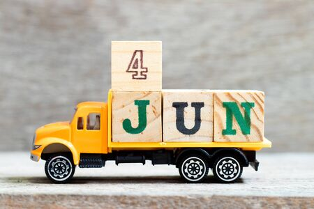 Truck hold letter block in word 4jun on wood background (Concept for date 4 month June)
