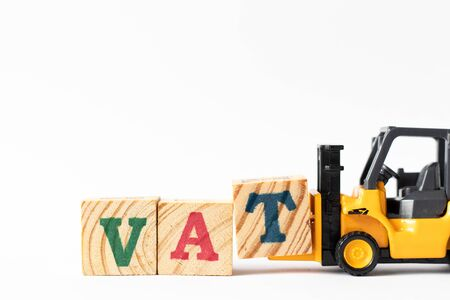 Toy forklift hold wood letter block T to complete word VAT (Abberviation of Value added tax) on white background