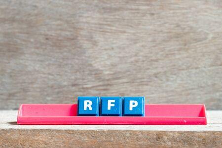Lettre de tuile sur support rouge dans word RFP (abréviation de demande de proposition) sur fond de bois